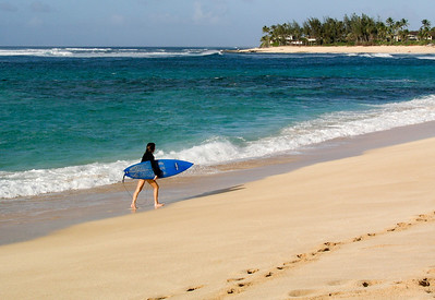 Surfer walking along Sunset Beach carrying his board