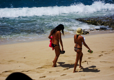 Girls in bikinis walking along the beach, Sunset Point, North Shore, Oahu, Hawaii