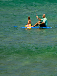 Father and daughter paddle surfing off Sunset Point, North Shore of Oahu, Hawaii
