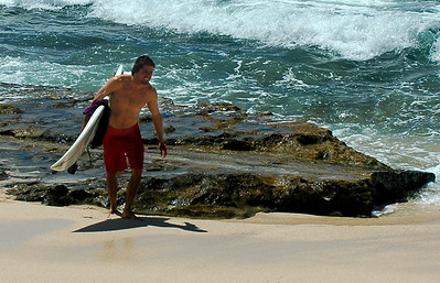 Surfer walking on the beach, carrying his board at Sunset Beach, North Shore, Oahu, Hawaii  2004