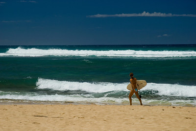 Female Surfer in a bikini walking on the beach at Backyards, North Shore, Oahu, Hawaii