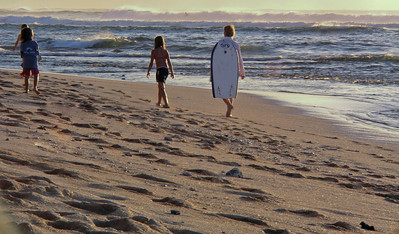Groms walking along Sunset Beach