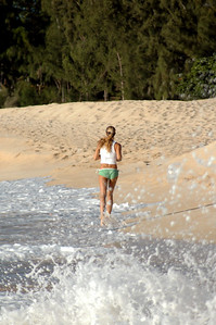 Pretty girl with a pony tail running along the beach  Sunset Beach, North Shore of O'ahu, Hawai'i