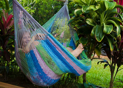 Woman in a colorful hammock amongst green
