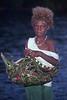 Village girl with basket of fish - Solomon Islands