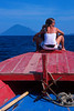 Lady riding on bow of traditional Indonesian boat in Bunaken Marine Preserve, Sulawesi.