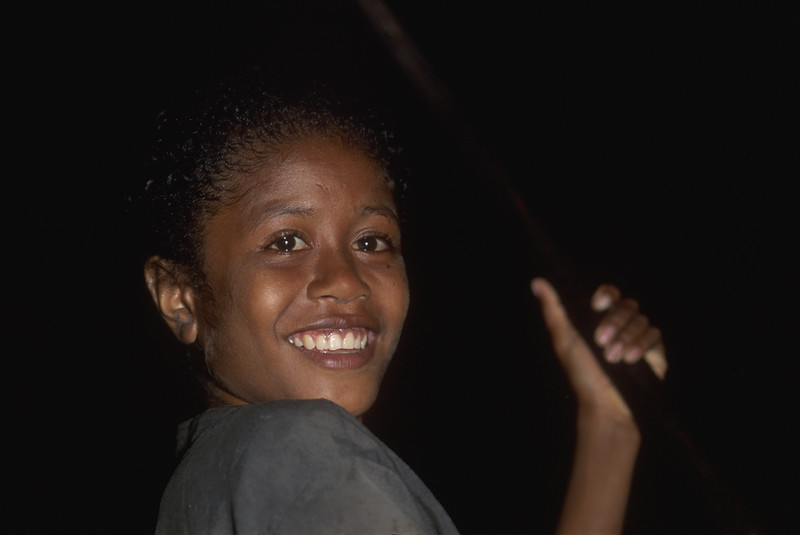 Village girl in dugout canoe at night - Milne Bay, Papua New Guinea