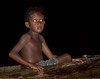 Village boy in dugout canoe at night - Milne Bay, Papua New Guinea