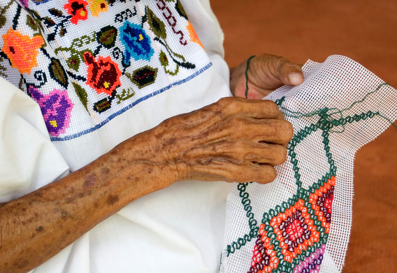 A mayan woman embroidering a huipil, a traditional woman's blouse.<br /> Santa Elena, Yucatan, Mexico