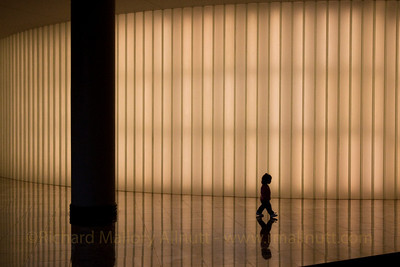 A young girl walks past a light installation in the World Financial Center in New York.