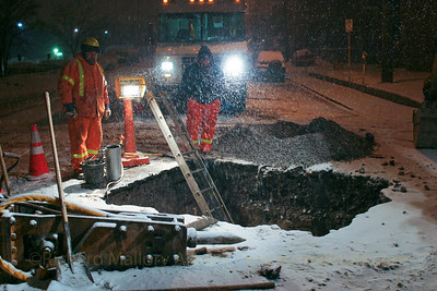Two workmen digging a hole in the road outside the Heart Institute in Ottawa, Canada. The hole came and went over the course of an evening, while my grandfather lay in intensive care inside the hospital following open heart surgery.
