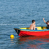 Children playing in colourful dinghy.