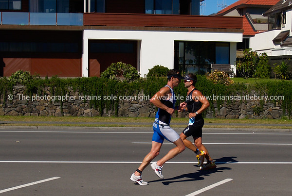 "Port of Tauranga Half Ironman, 2011, two runners pass in opposing directions. Tauranga is New Zealands 5th largest city and offers a wonderfull variety of scenic and cultural experiences. ALSO SEE; <a href=""http://www.blurb.com/b/3811392-tauranga"">http://www.blurb.com/b/3811392-tauranga</a><br /> Check our ""EVENTS"" galleries for heaps more; <a href=""http://www.brianscantlebury.com/Events"">http://www.brianscantlebury.com/Events</a>"