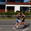 """Port of Tauranga Half Ironman, 2011, two runners pass in opposing directions. Tauranga is New Zealands 5th largest city and offers a wonderfull variety of scenic and cultural experiences. ALSO SEE; <a href=""""http://www.blurb.com/b/3811392-tauranga"""">http://www.blurb.com/b/3811392-tauranga</a><br /> Check our """"EVENTS"""" galleries for heaps more; <a href=""""http://www.brianscantlebury.com/Events"""">http://www.brianscantlebury.com/Events</a>"""