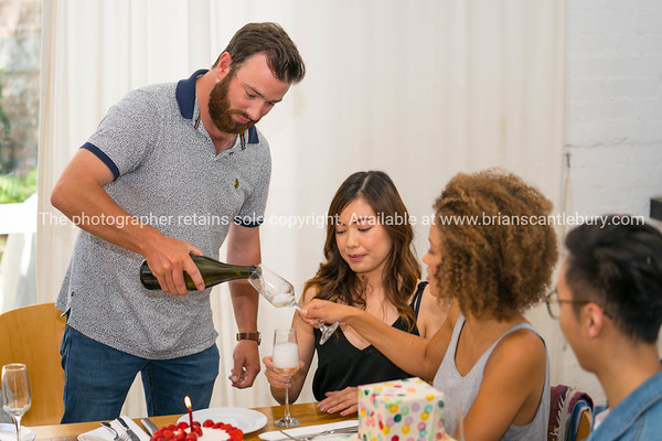 Four people sit around table withgifts and food