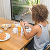 Young woman checking her mobile phone social media over breakfast table.
