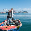 Tauranga Port and fisherman extra-ordinaire, Darrin Jones in dinghy holding up kingfish just caught.