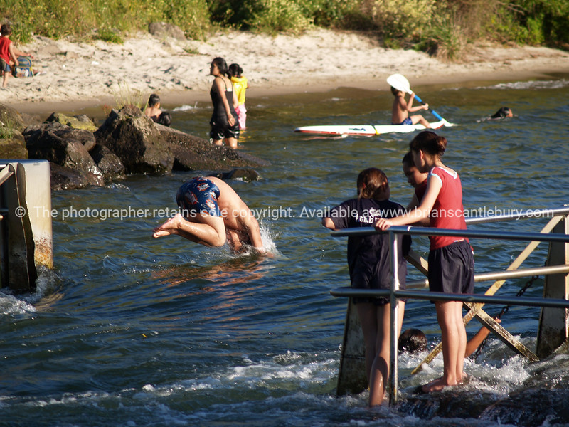 Enjoying the summer, swimming, diving. New Zealand photographic stock images.<br /> Model Release; no.