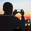 Grainy mobile phone image of silhouetted man taking photo of sunset with mobile phone