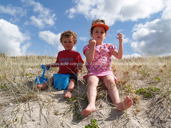 Two small children at Papamoa on sand dunes.<br /> Model/property release; Yes