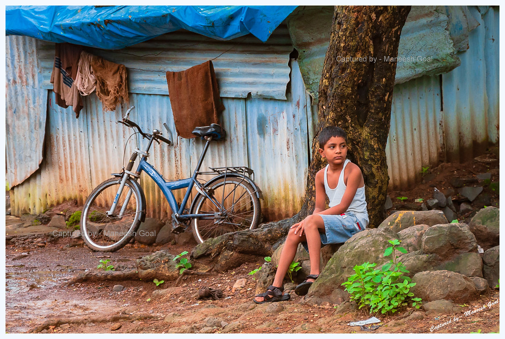 Whither Childhood?<br /> <br /> This is a picture that I took recently on a rainy Sunday morning while out on a nature walk inside the Sanjay Gandhi National Park, Mumbai. While I was strolling inside the park and enjoying the greenery, I came across a house where a boy, seated outside on the rocks, was quietly observing a heated conversation between two people. As I observed closely, I saw that his face was melancholic (probably saddened by the commotion), he was poorly dressed and was looking in a direction away from the bicycle leaning against the house. That's when I took this picture...<br /> <br /> Later when I saw the picture on the camera's LCD, it seemed to convey a totally different story (or as any third person who was not present at that moment would wonder) - one of a boy perhaps reflecting upon his lost childhood! The boy would have been out cycling or playing with other kids on any other Sunday morning, but something was holding him back today, something had saddened him. Was it the end of his childhood? Would he soon have to head out in search of work to meet household expenses? Is he going to miss his school in order to work? Or was it that his house was going to be relocated outside the national park and he would miss the surroundings where he spent the best days of his childhood? Or was it just that he was waiting for the sun to come out so that he could play? Or was he just unwell that day and hence appeared weak and sad? <br /> <br /> Pictures such as these have the power to create a well of emotions inside us...words will never be able to achieve that!