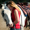 Young woman rider shows her horse her gratitude after a gymkana