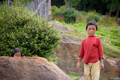 Not everybody is a cooperative subject - note the girl hiding behind the rock! Phobjikha, Bhutan