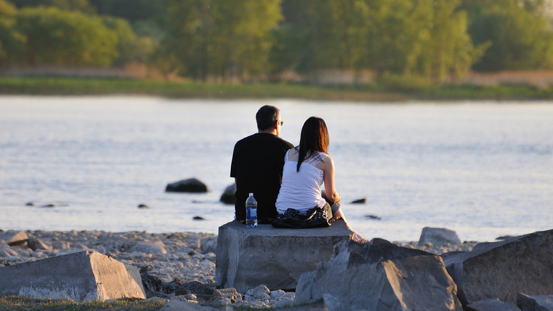 A young couple contemplatiing sunset time facing water