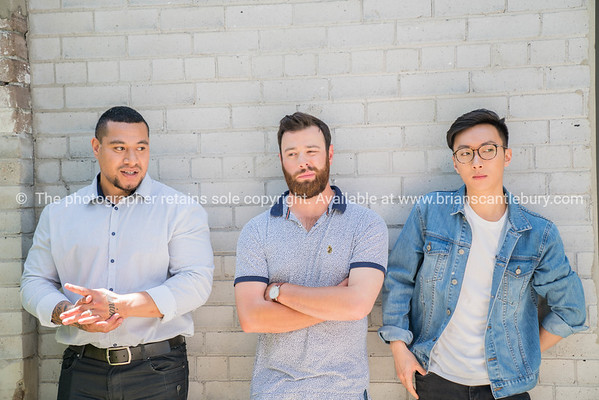 Three mixed race males lined up against brick wall.