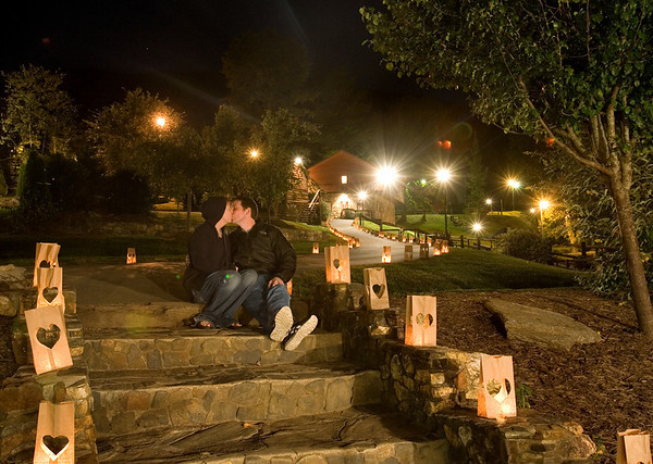 A young couple smooch on stone steps at a couple's retreat in the mountains surrounded by heart shaped luminaries.  (Jenni Farrow)