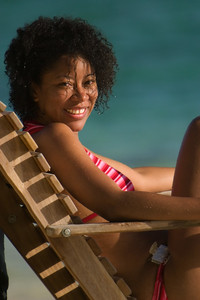 Beautiful young woman relaxing in lounge chair on south beach at South Water Caye, Stann Creek, Belize.