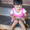 Small child sitting on step with thanaka on face. Myanmar Travel Images