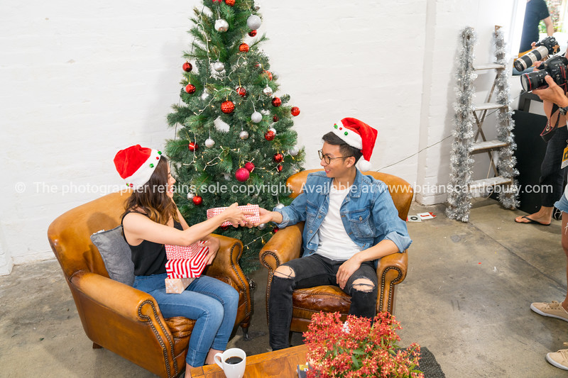 Under Christmas tree, young couple on Christmas morning.