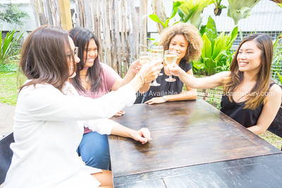Four women sitting around outdoor table celebrating and haing drink.