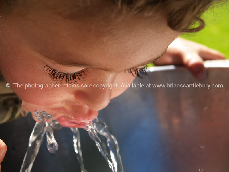 Child sips at the fresh clean cool water from a water fountain.                                                                 <br />  Model Release; Yes.