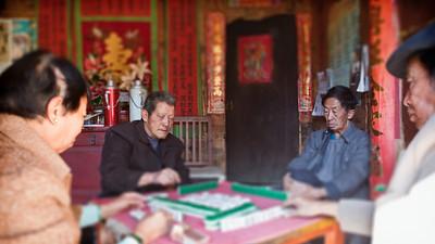 Yang Zheng Qi (l) and Yang Wen Hu (r), both 73, playing majong at the hidden courtyard.  Natural light, tilt shift