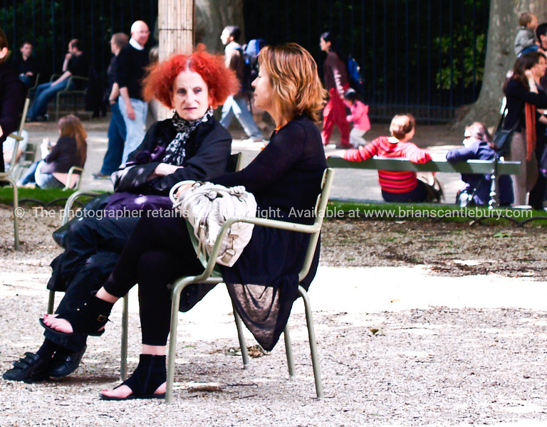 Redhead, and friend seated in Paris park. Grounds of Luxembourg Palace on a Sunday afternoon. Model Release; No. Editorial or personal use only.