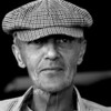 Black and white photo of an older man in a checked cap