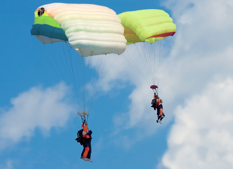 Brightly colored parachutes drop through the air as tandem jumpers make their first jumps