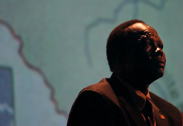 Simon Deng, sits in front of a map of Sudan, his native homeland and place of his former enslavement.  Monday evening at ECU's Hendrix Theatre he gave a lecture on 21st Centure Slavery, bringing awareness and calling for change.  (Jenni Farrow)