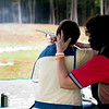 Woman taking rifle gun shooting lessons