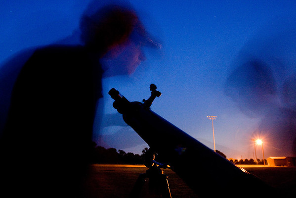 Carolina Skies Astronomy Club member Benjamin Prosser, 13, helps Jonathan Hurst, 7, and his family set up their telescope Saturday night at the Bradford Creek Soccer Complex.  (Jenni Farrow)