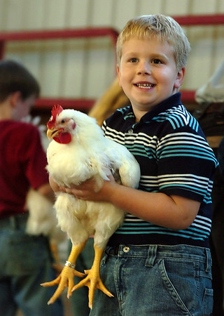 """William Snowden 6 smiles at his parents after receiving a blue ribbon Monday night at the Pitt County Fair for his rooster 'Charles'.  """"I have to tell you, I love my chicken.  I'm glad I showed him"""" said Snowden who participated with his sister Heather 7.  <br /> (Jenni Farrow)"""