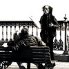 Black and white photo of a painter persuading a couple of young lovers to pose