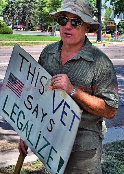 A military veteran holding a political sign.