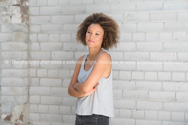 Beautiful Hispanic young woman standing by brick wall