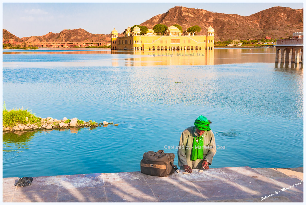 A man prepares food for the fish near the Jal Mahal Complex, Jaipur (Rajasthan)