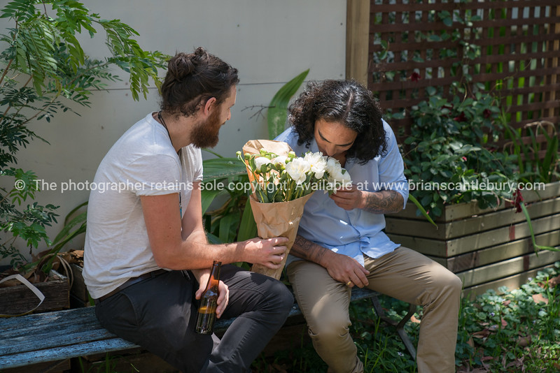 Two hip young men with bunch white roses.