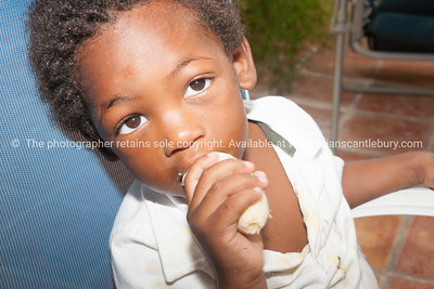 Small black boy eating. Model release; No.