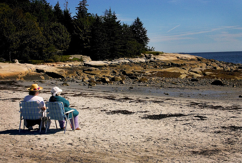 Elderly ladies sitting on the beach on a sunny afternoon in Maine
